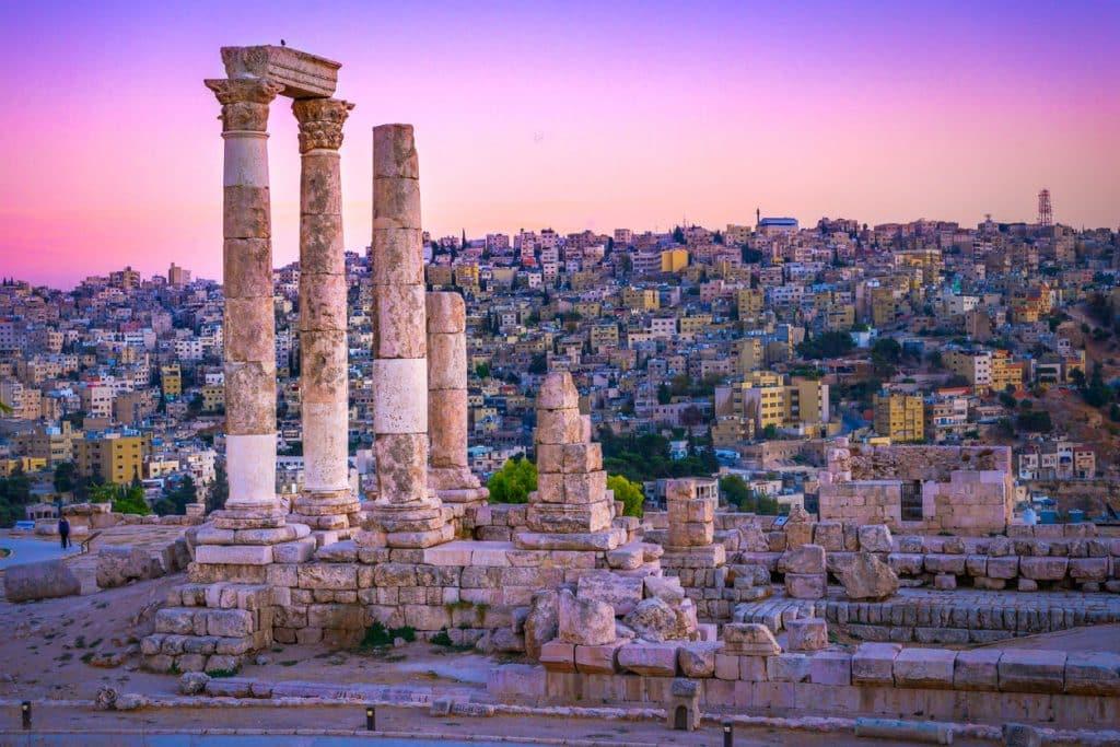 Закат в Аммане с историческими колоннами и видом на город.