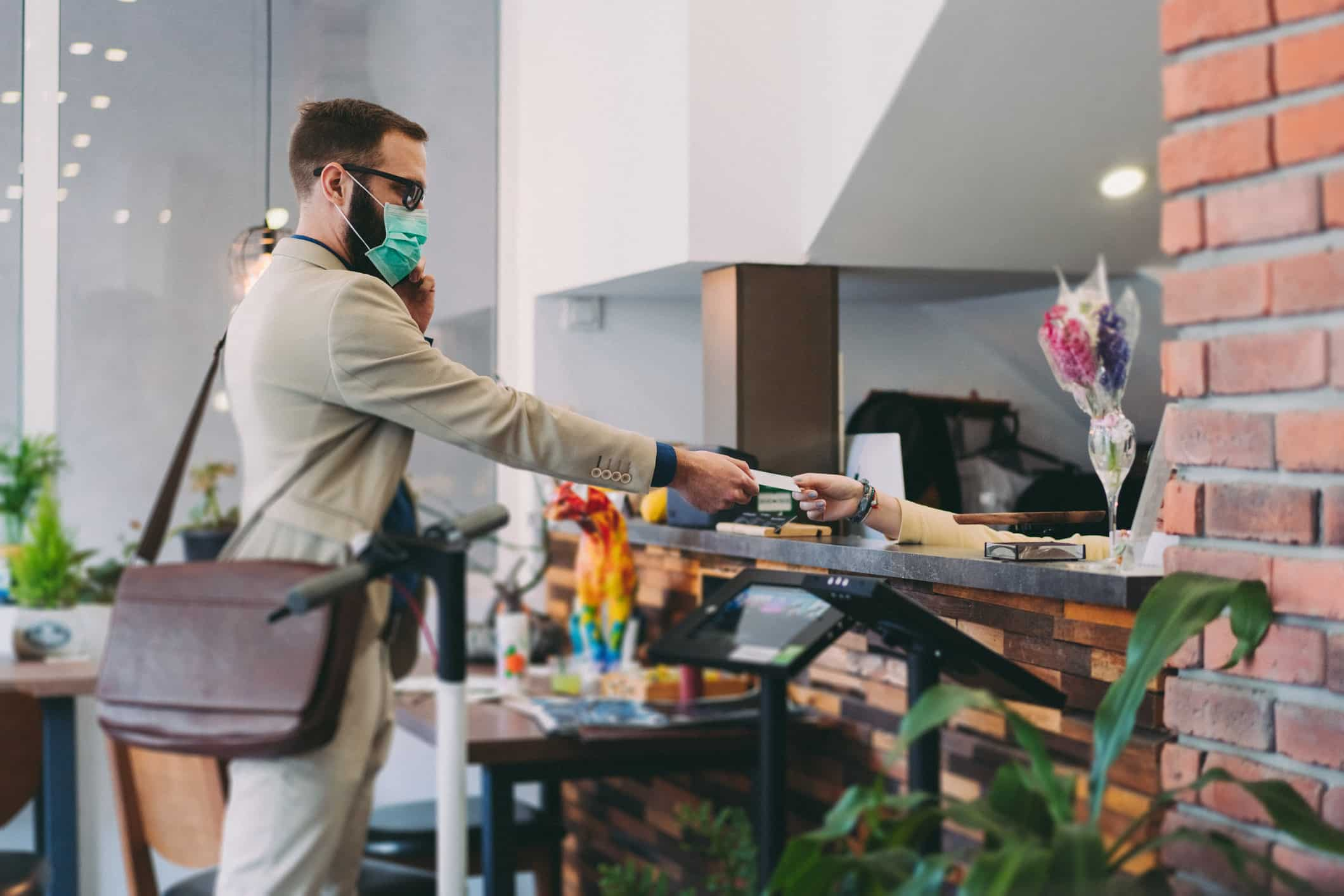 Man wearing a mask checking in to a hotel