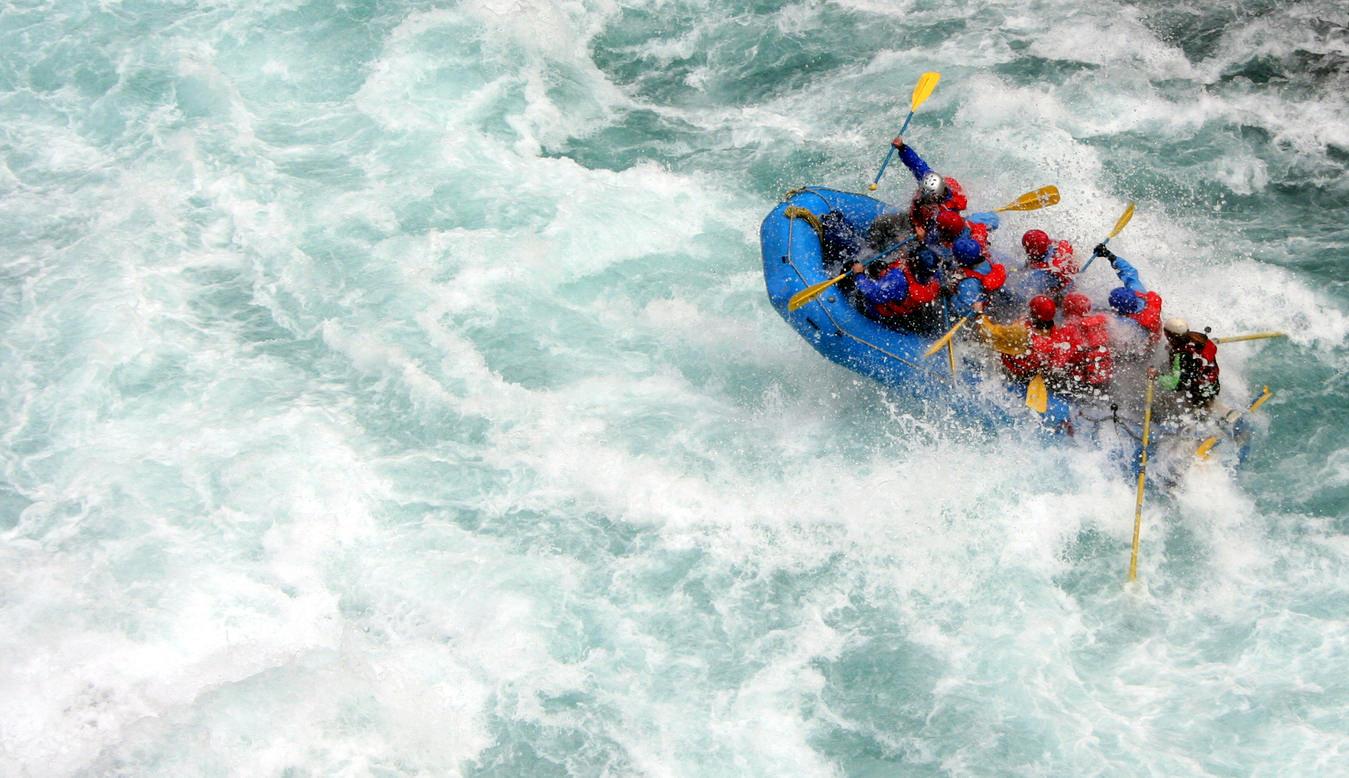people rafting in fast-flowing water