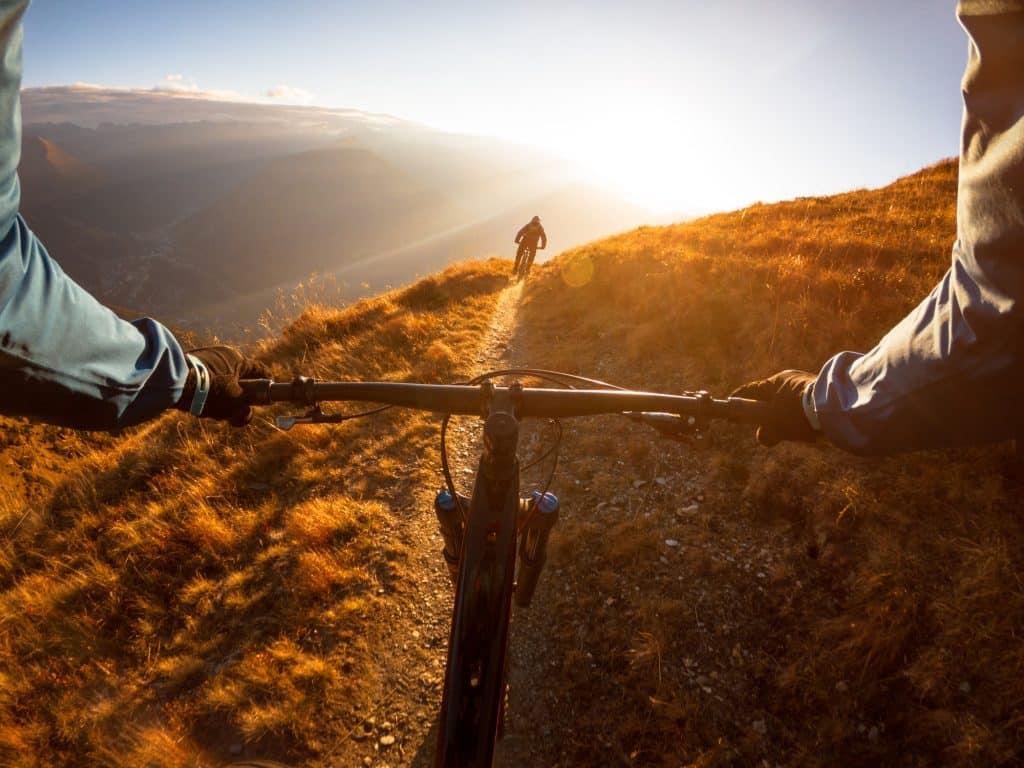 A cyclist on a hillside path.