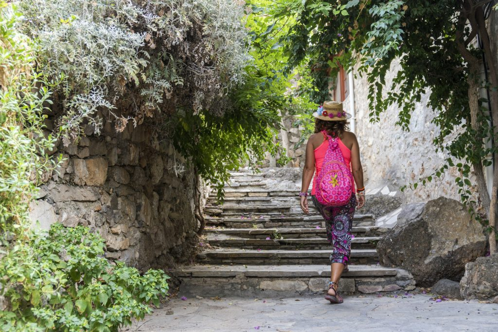 Woman with backpack walking on quiet streets in Datça