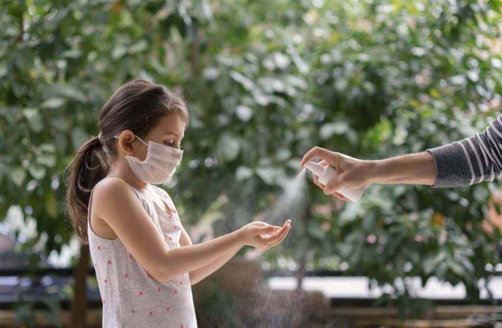 Father spraying sanitizer onto the hands of his daughter